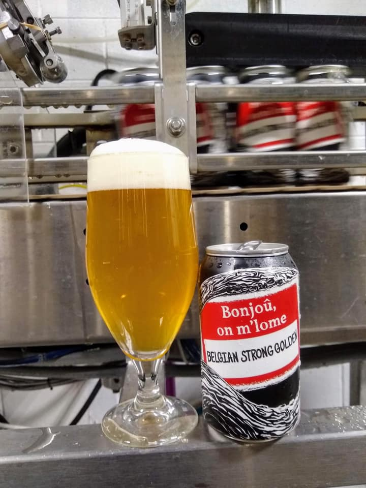 Glass and can of Belgian Golden Strong, in front of canning equipement
