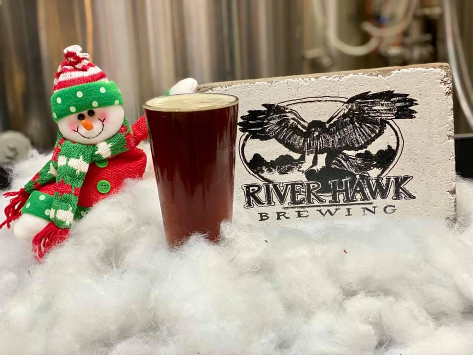 A cute snowman, a River Hawk Decoration, fake snow, and a glass of River Hawk's Toboggan Ride - their latest beer.
