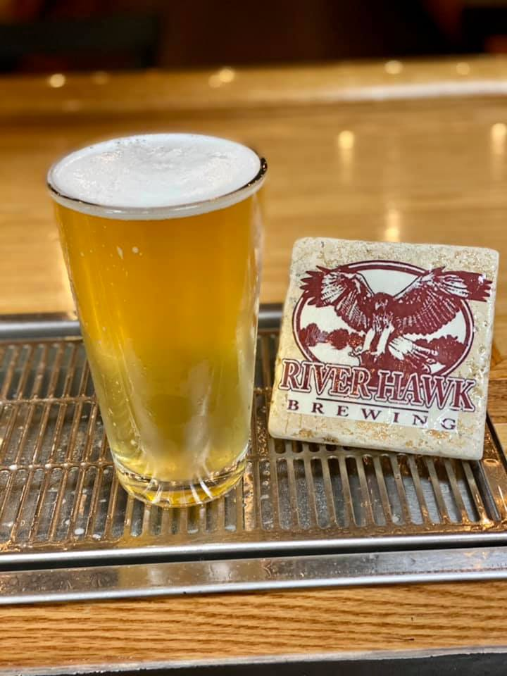 A pint glass of beer next to a River Hawk Brewing coaster.