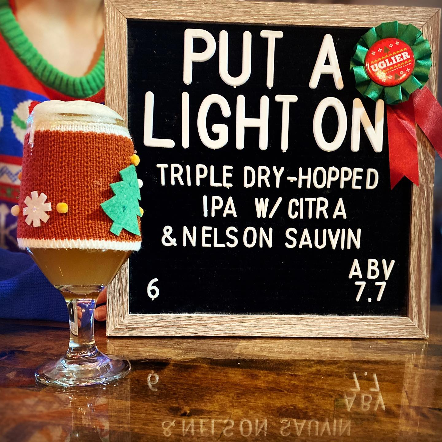 Glass fof beer in holiday sweater.  Information about beer on a letter board in background.
