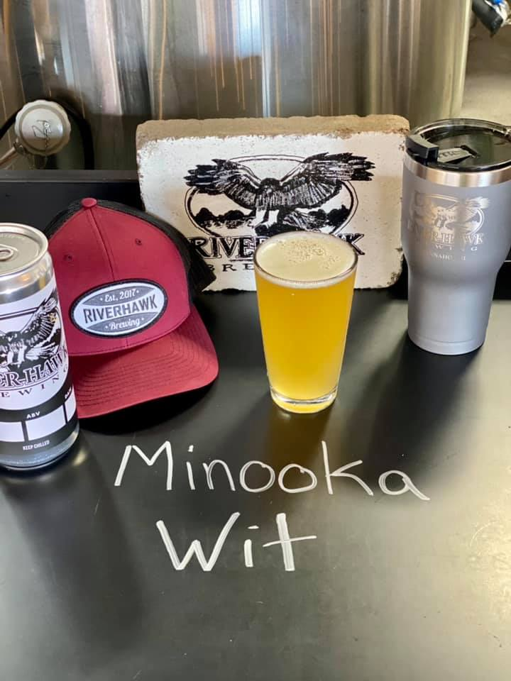 Glass of Minooka Wit, surrounded by River Hawk Brewing