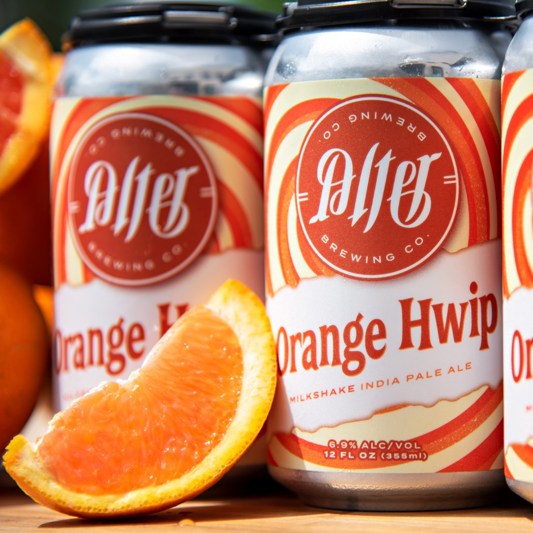 Two cans of Orange Hwip from Alter Brewing Company, next to an orange slice