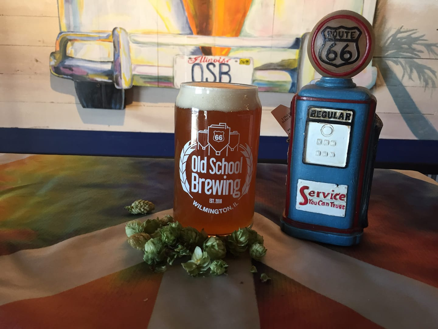 A glass of The First Days from Rt66 Old School Brewing, next to a mini replica Rt 66 Gas Pump