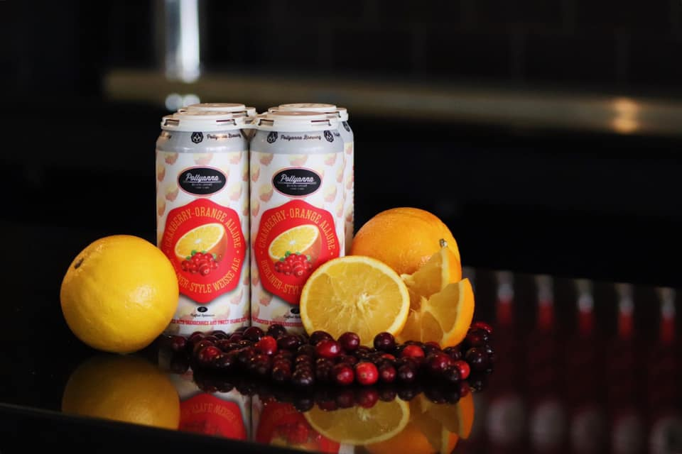 Four pack of Cranberry Orange Allure by Pollyanna Brewing company, surrounded by oranges and cranberries