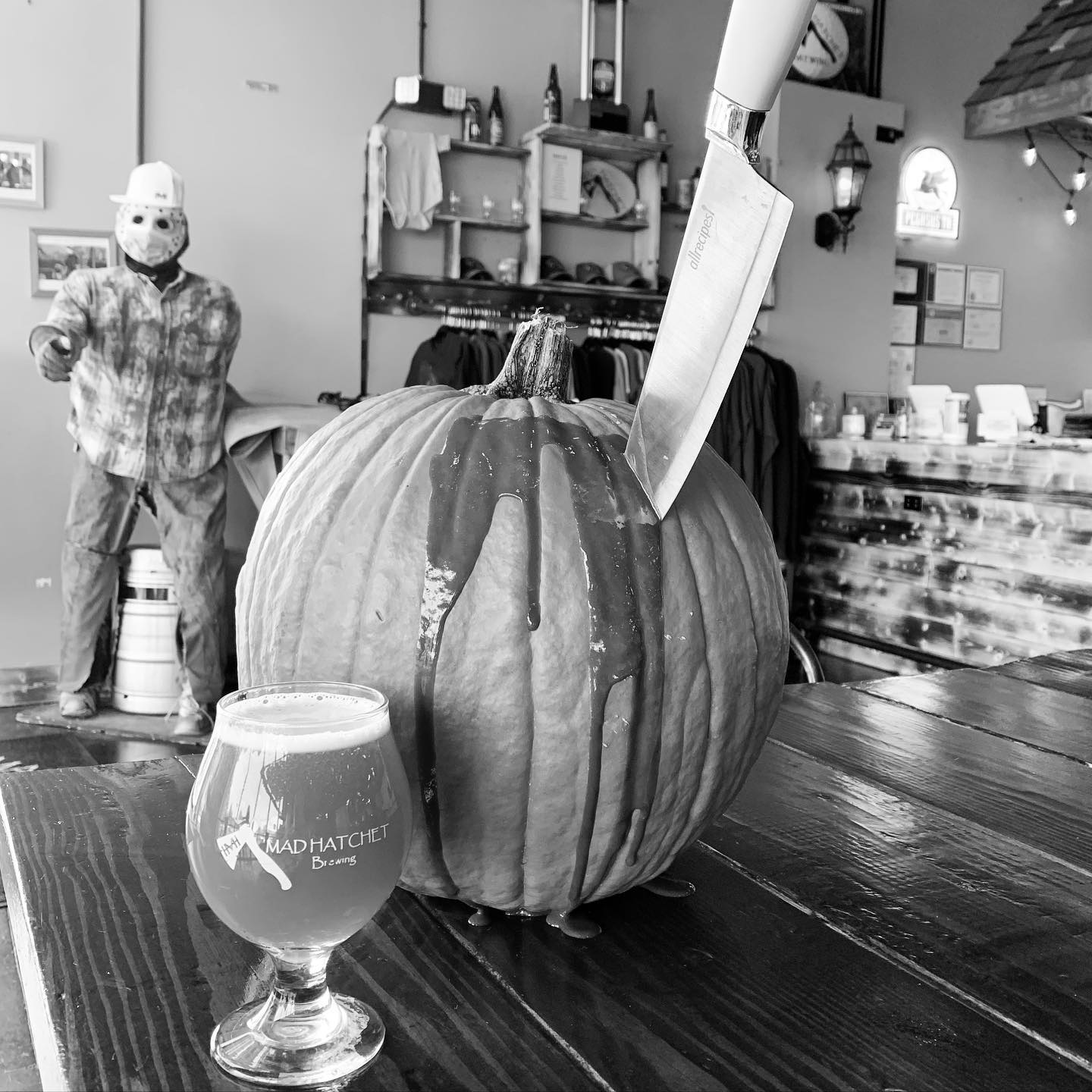 Pumpkin with knife plunged into it, beer in foreground