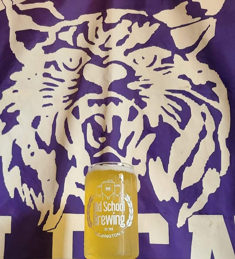 Rt66 Old School Brewing's Wildcat Cream Ale in a glass, in front of a flag of a wildcat (school logo)