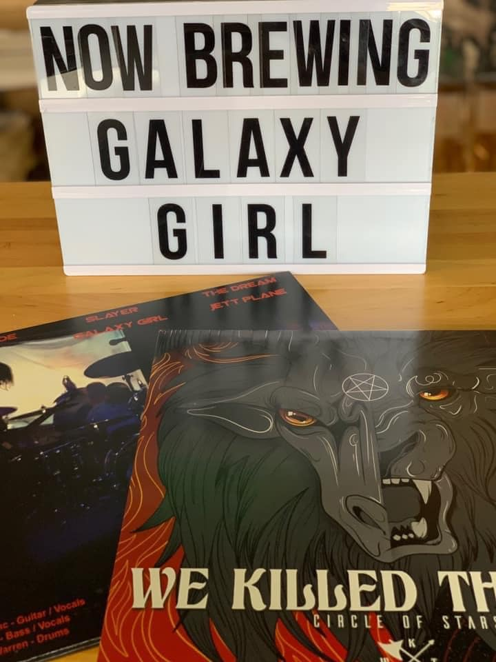 Sign that says Now Brewing Galaxy Girl, with an album from We Killed The Lion in the foreground