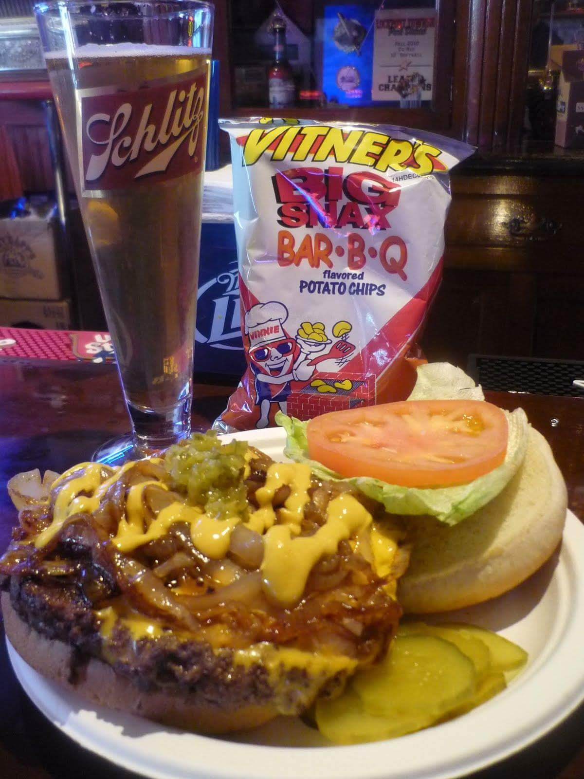 Nick's burger with a bag of bbq chips and a cup of beer.