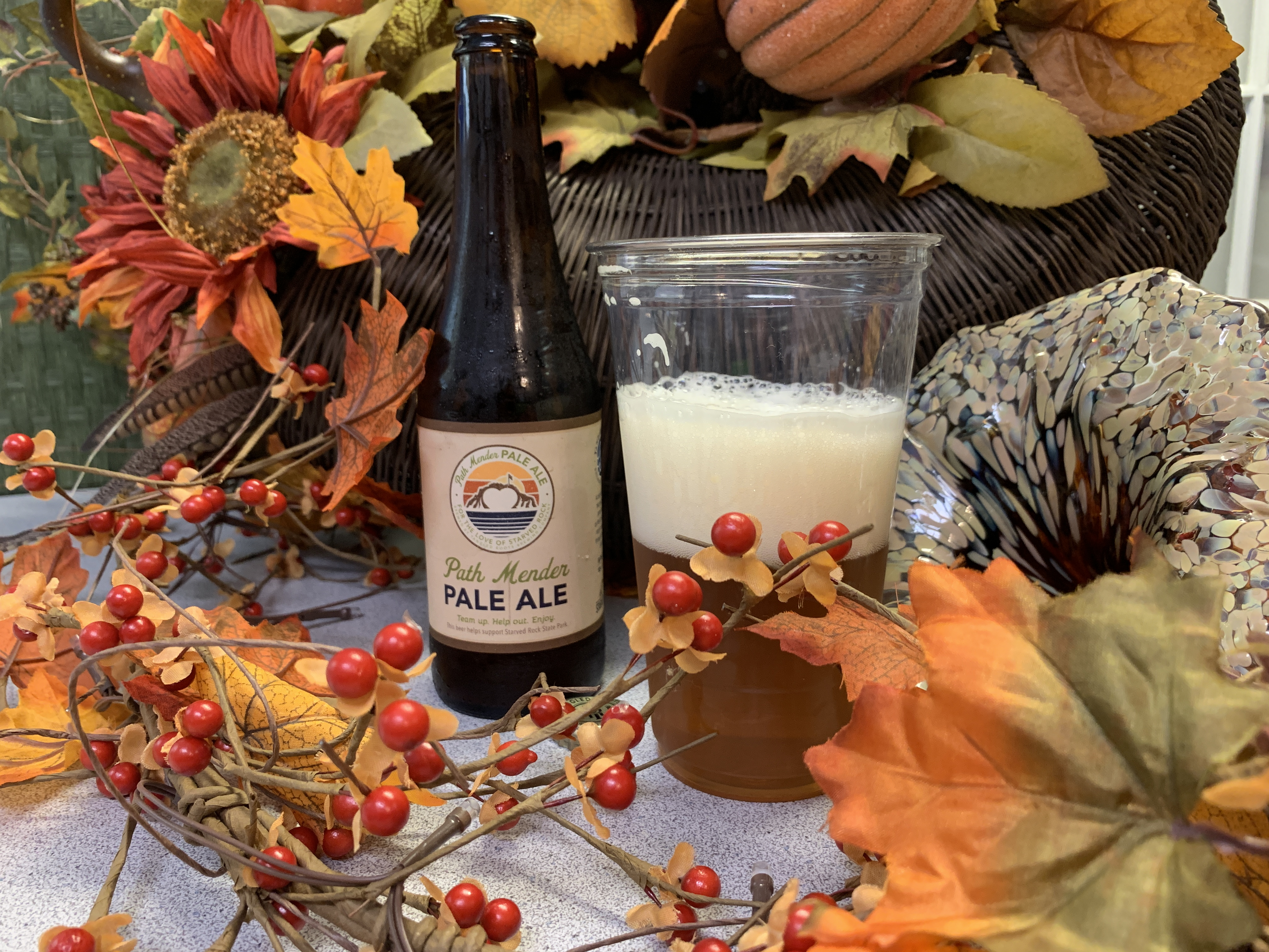 Path Mender bottle of beer next to a cup of the beer, surrounded by fall decor