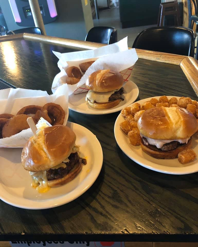 Three burgers, two with a side of onion rings and one with tater tots
