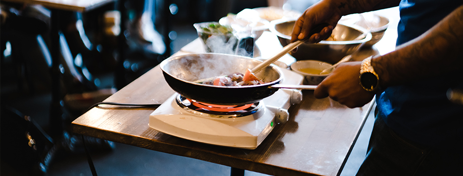 a chef cooking food in a skillet