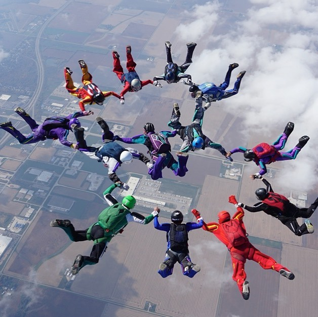 a group of skydivers holding hands in a circle in the air