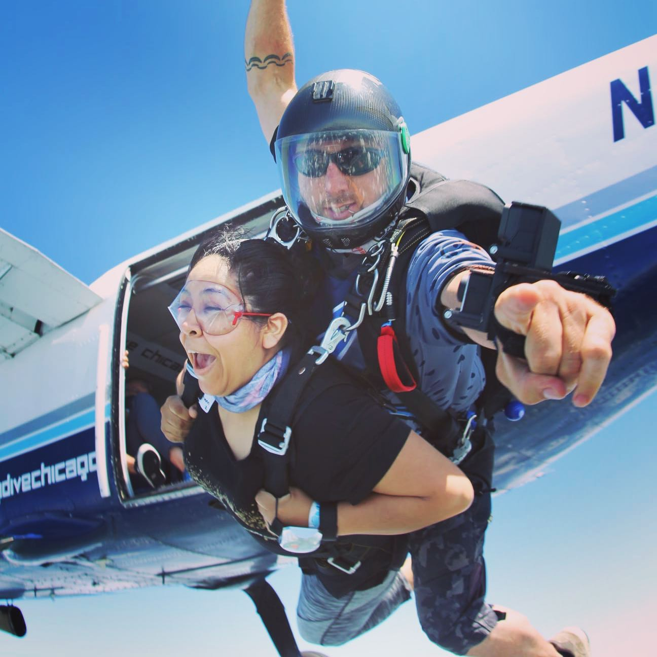 someone harnessed to an experience skydiving jumping out of a plane