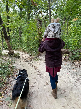 a parent and child sitting on their shoulders walking through the trails of starved rock with dog on leash