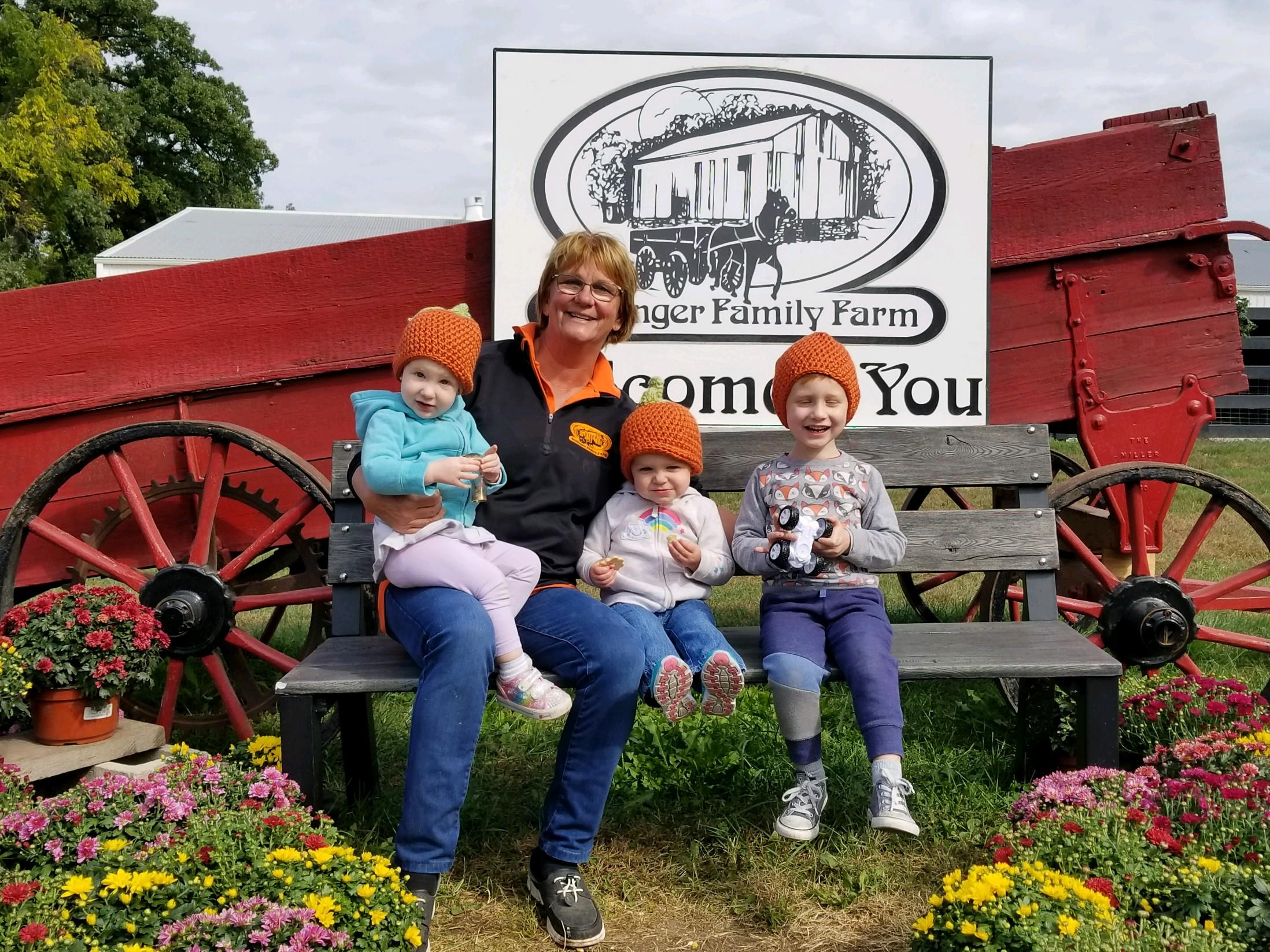 Noreen Dollinger with her three grandchildren in from of their welcome sign