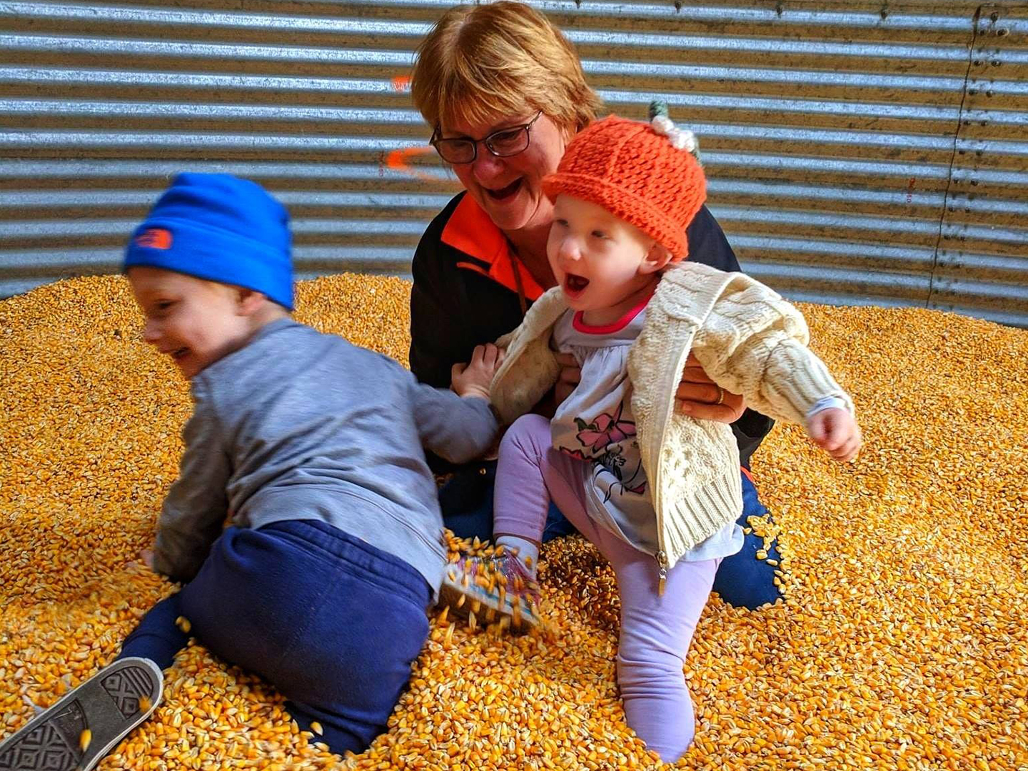 Noreen with her two grandkids playin inside the corn pit