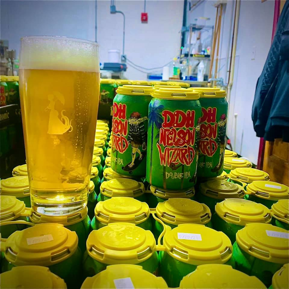 Glass and four pack of cans of Miksatonic's DDH Nelson Wizard, on top of a pallet of cans