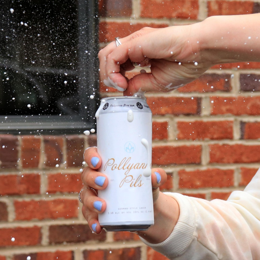 Someone opening a can of Pollyanna Pils, with some foam spitting out