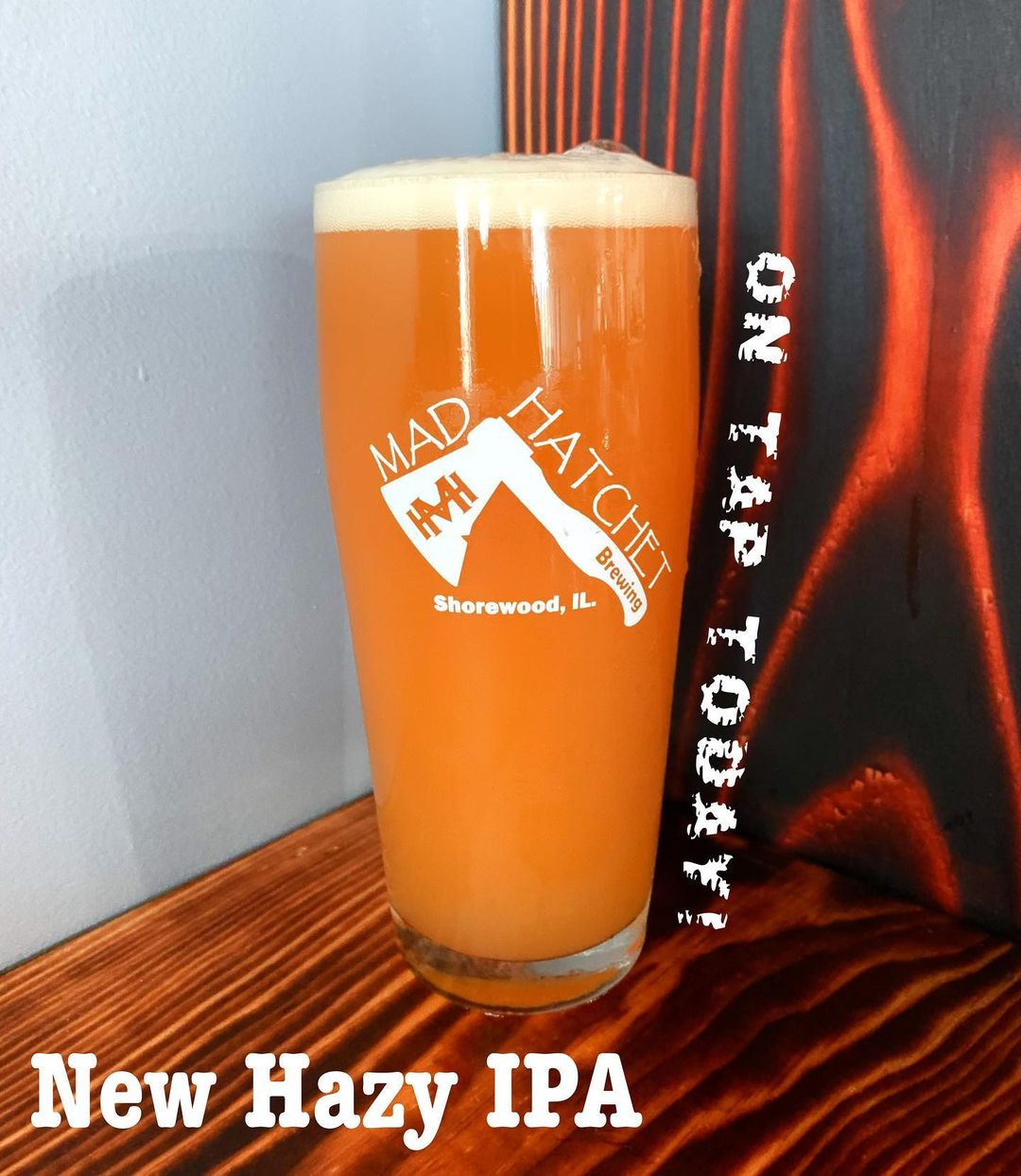 Glass of orange beer with text on tap today . new hazy ipa .. .from Mad Hatchet