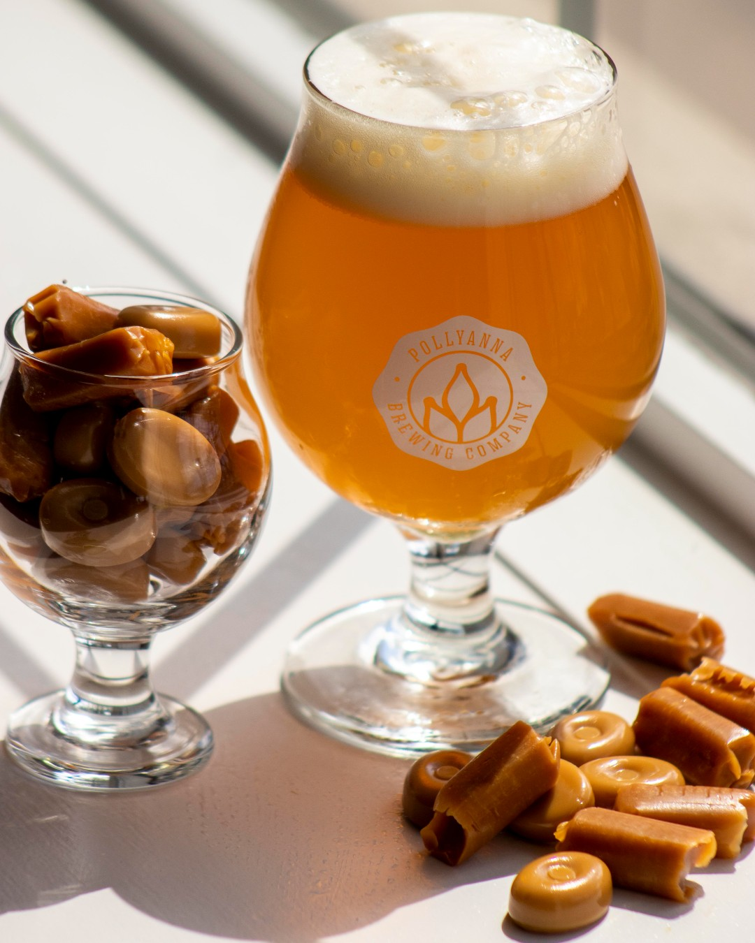 Glass of Pollyanna beer surrounded by caramel candies
