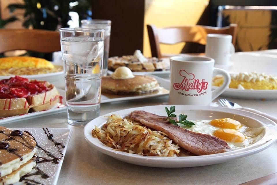 hashbrowns, ham, eggs, waffles, pancakes and coffee on a table
