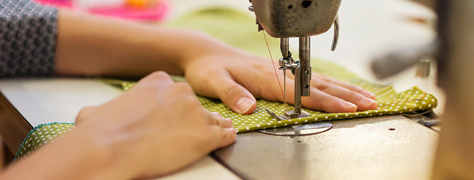 someone using a sewing machine to make a garment with green polka dot material