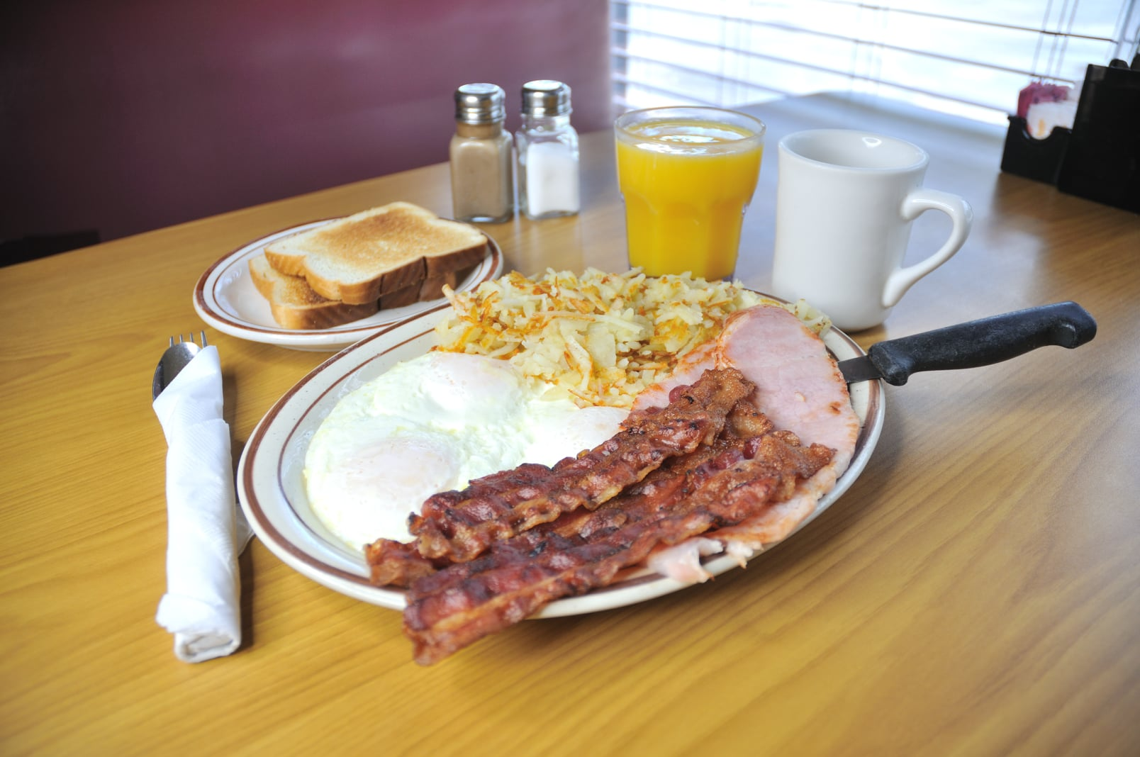 fried eggs, bacon, hame, hash browns, and toast with a cup of coffee and orange juice
