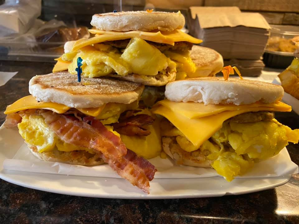 three breakfast sandwiches stacked on top each other made with eggs sausage and bacon