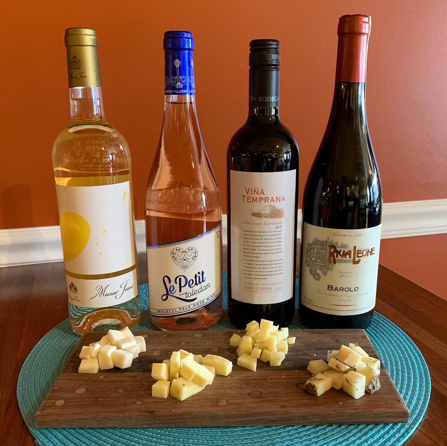 4 bottles of wine next to a board of cut up cheese