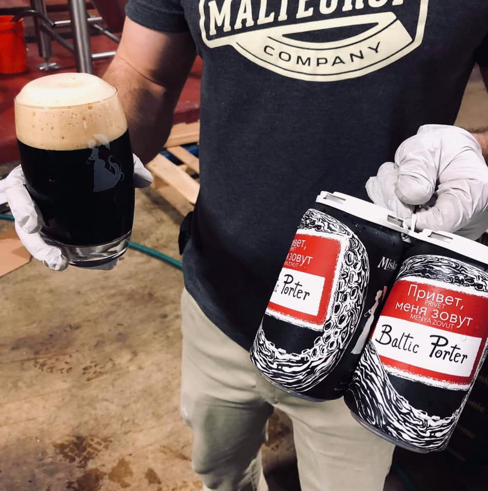 brewer holding a glass, and a four pack, of baltic porter