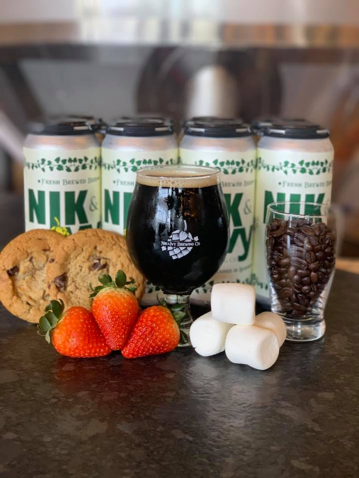 Nik & IVy's Chocolate Fondue Beer (surrounded by a glass of cocoa beans, marshmallows, strawberries, and  four cans)