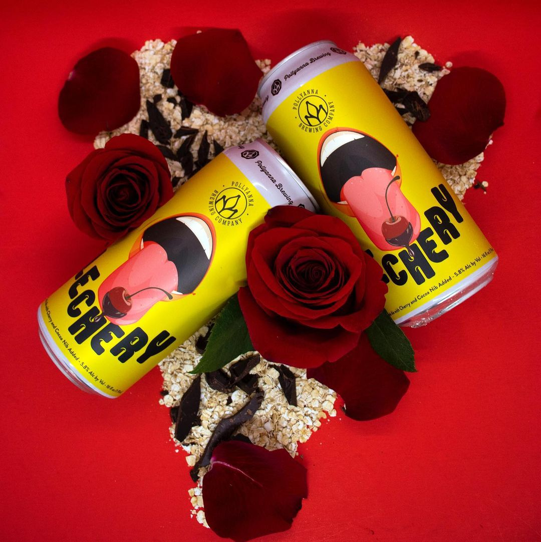 Cans of Lechery, surrounded by roses, cocoa nibs, and oatmeal.
