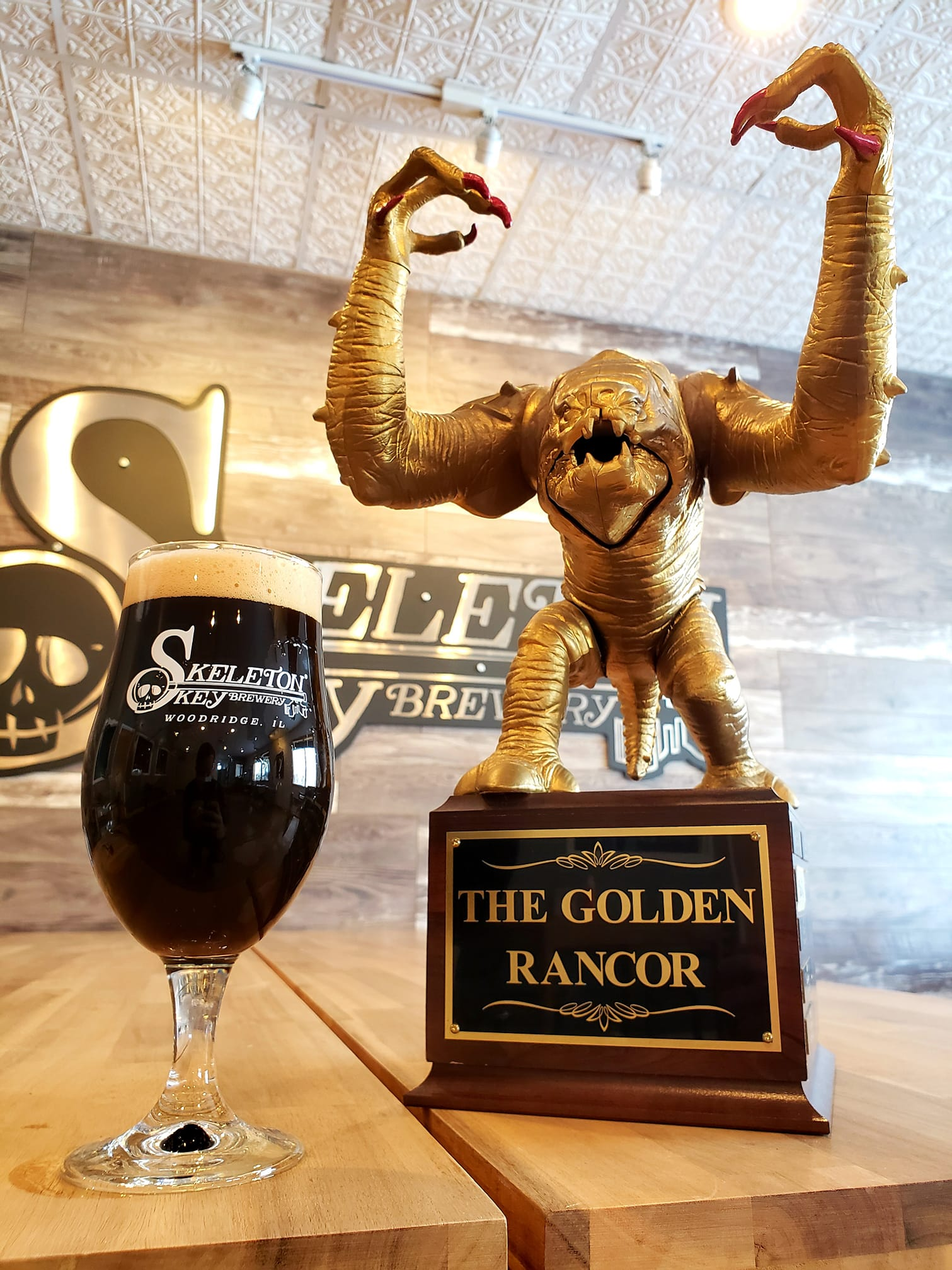 Glass of Plan for Everything from Skeleton Key Brewery next to the Golden Rancor trophy