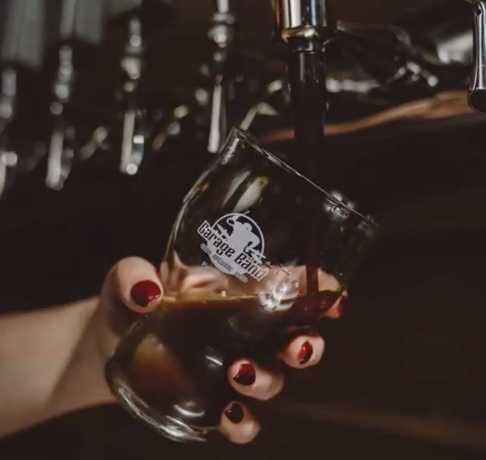 Beer flowing from a tap into a glass at Garage Band Brewing