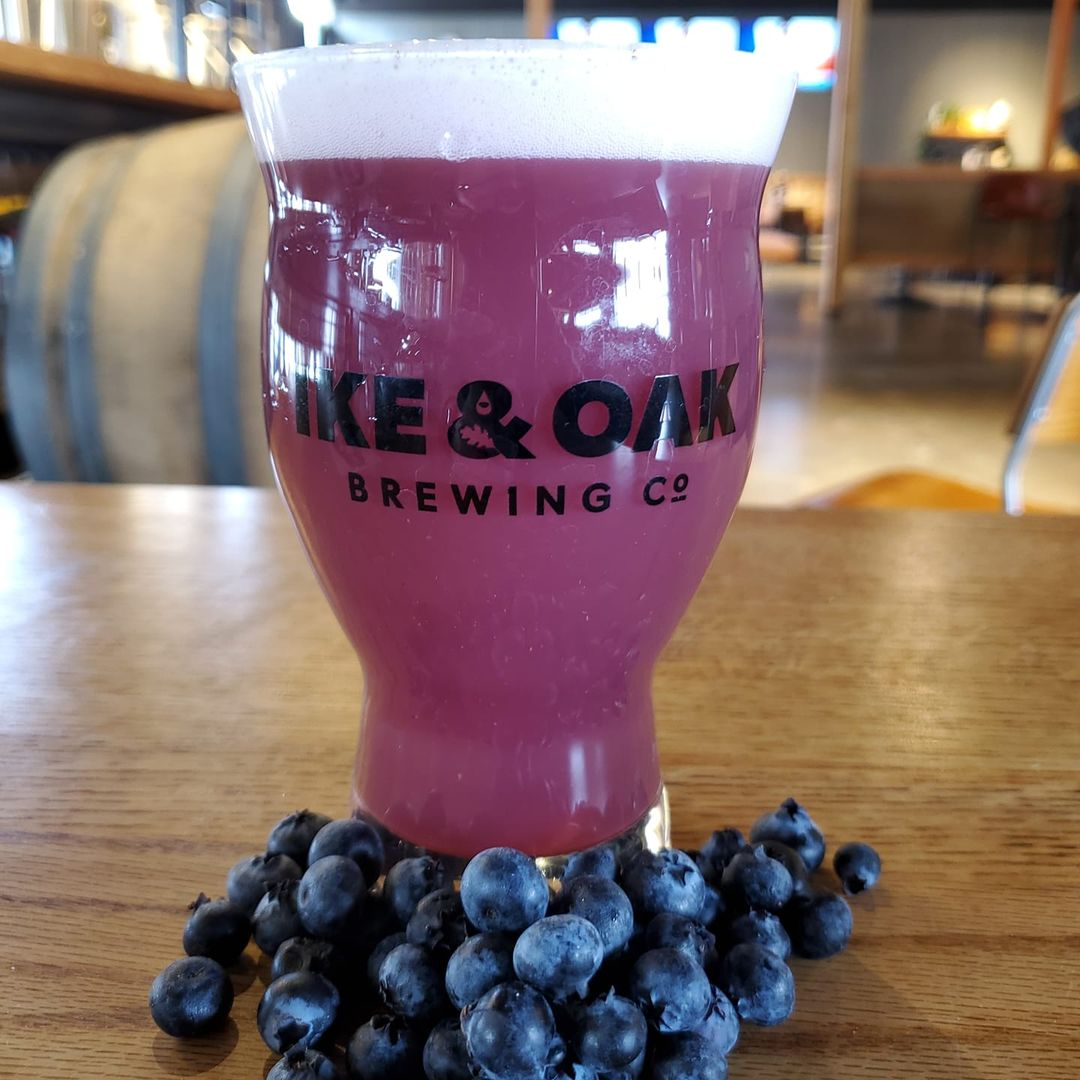 Tall glass of Woolly Harbor from Ike & Oak, surrounded by blueberries