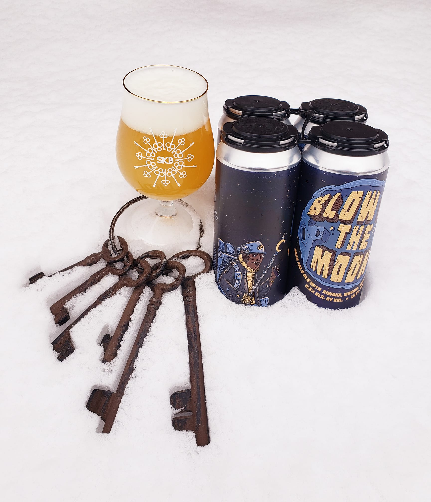 A four-pack of beer and a glass in the snow, along with a key ring featuring old fashioned keys