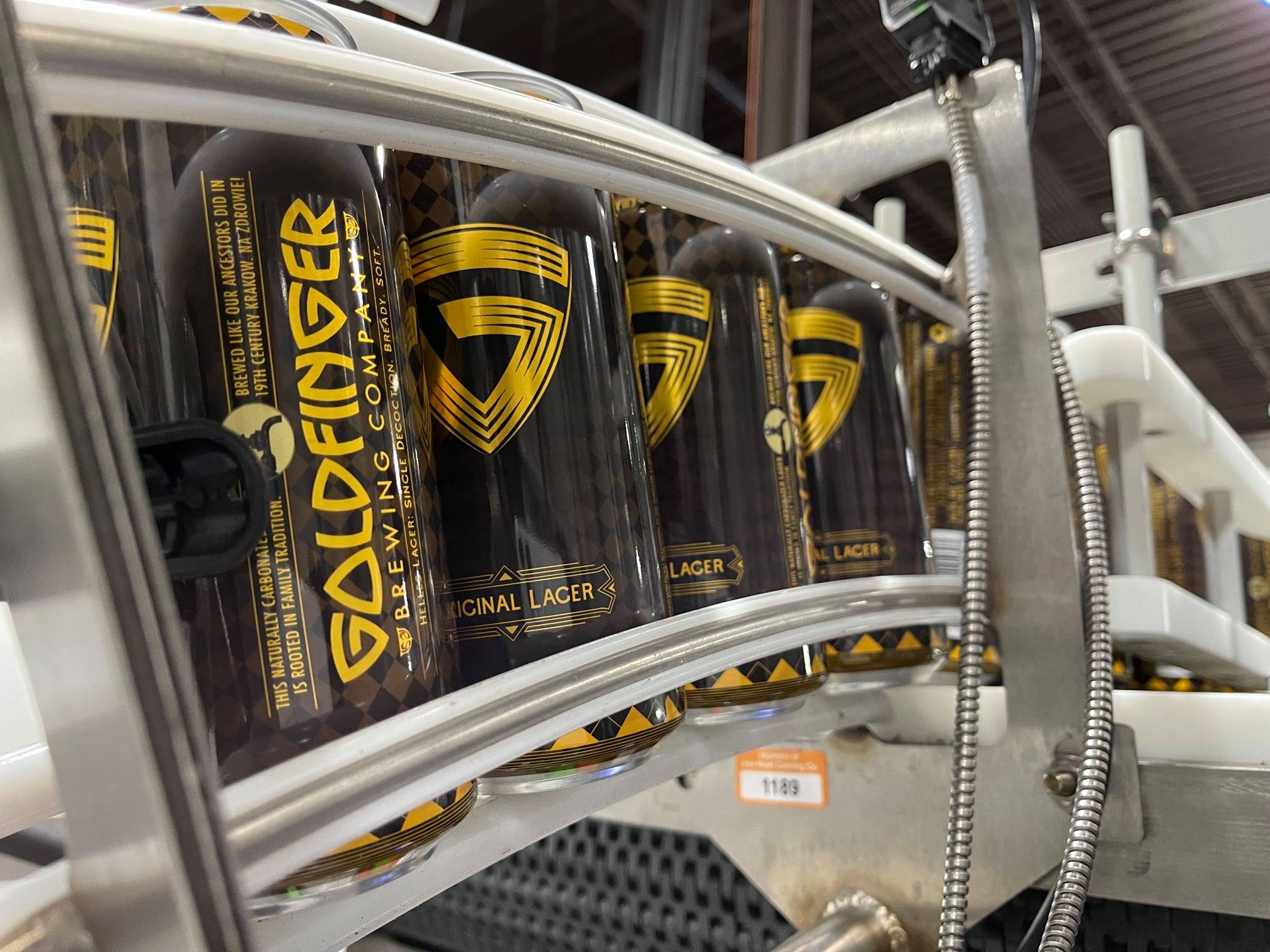 Black Goldfinger Cans on the canning line at Goldfinger Brewing Company