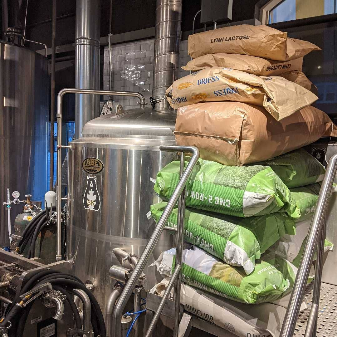 bags of ingredients next to a brewing vessel at Ike and Oak Brewing