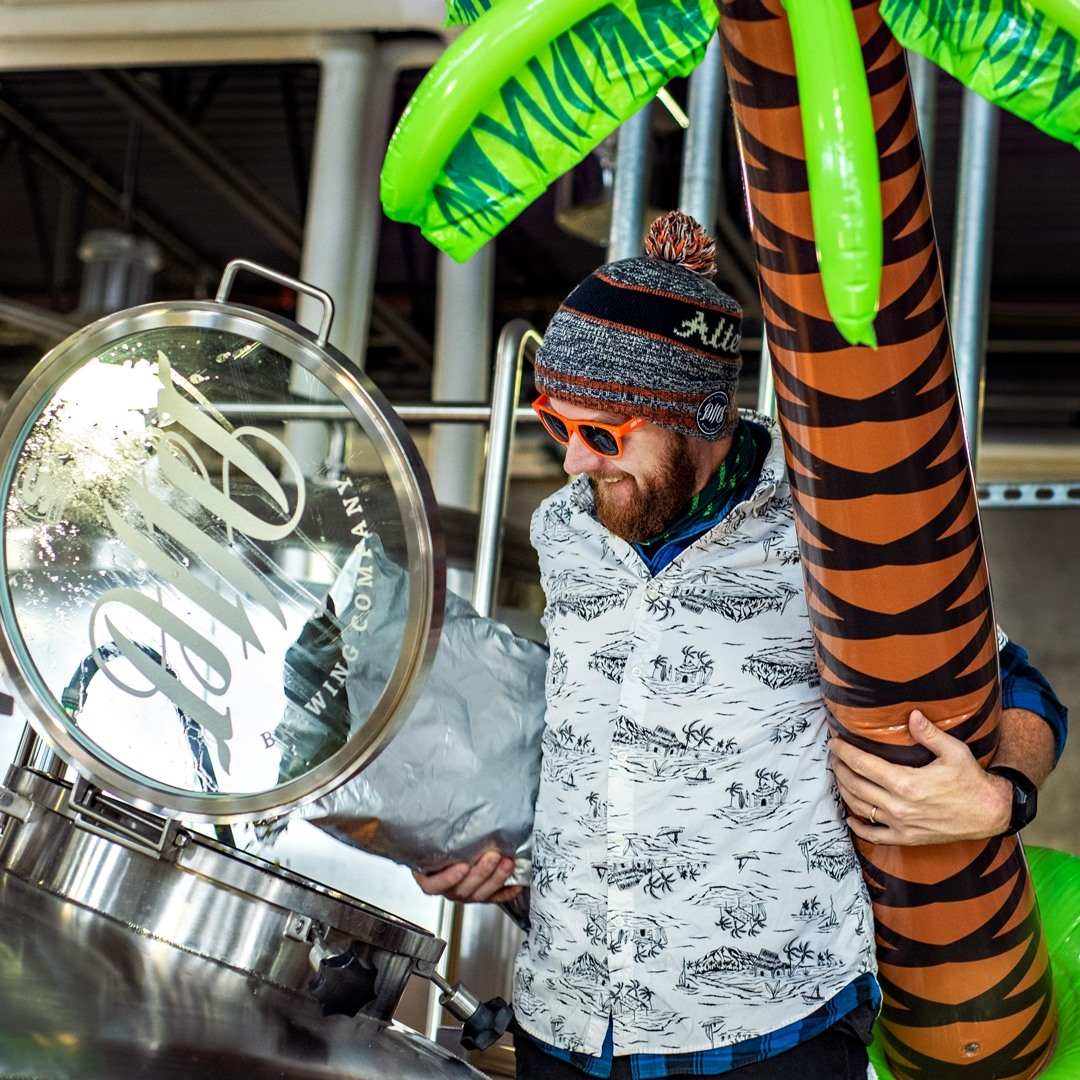 Brewer holding a giant inflatable palm tree