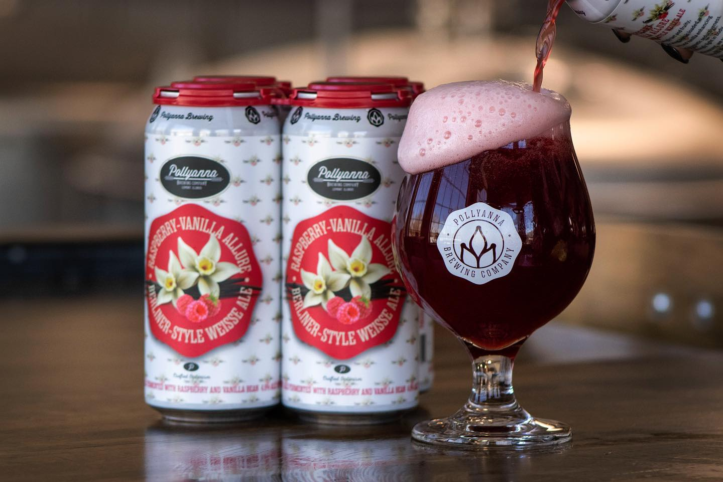 Four cans and a glass of Raspberry-Vanilla Allure from Pollyanna Brewing Company