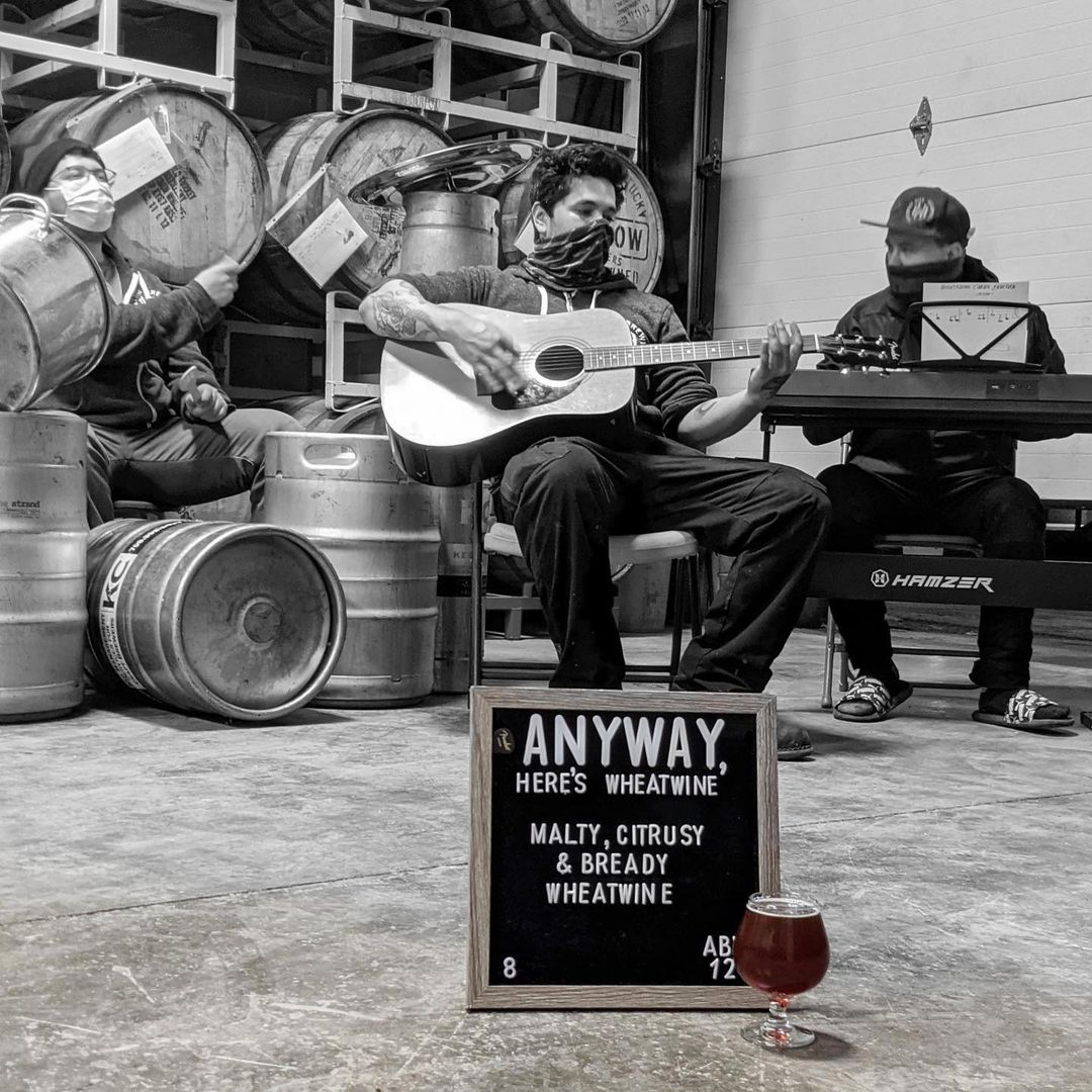 brewers playing in front of barrels at Whiskey Hill Brewing