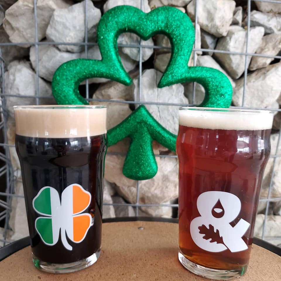 Glasses of two different beers, in front of a clover decoration
