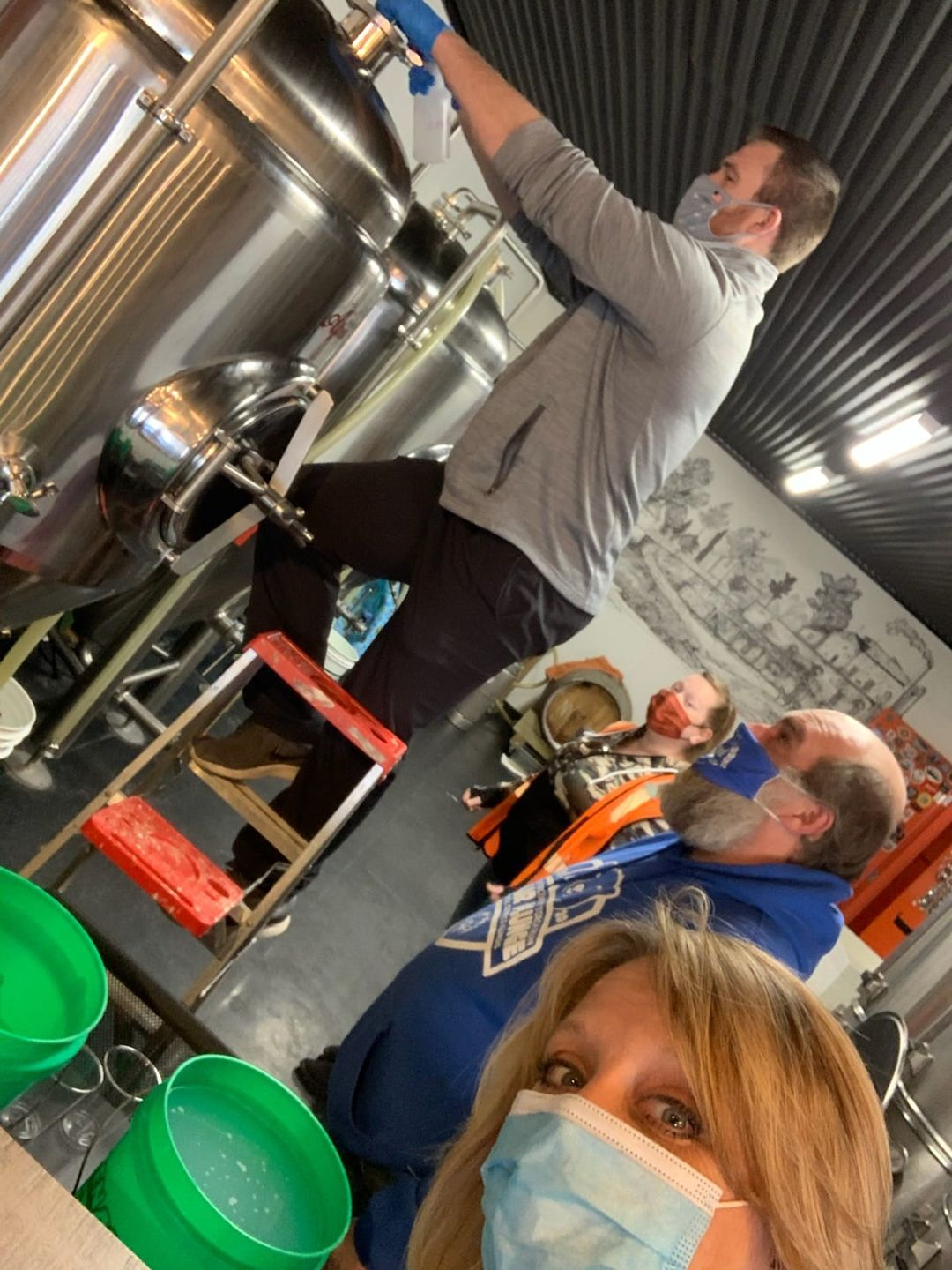 One brewer pouring ingredients into a vessel.  Some looking on, one looking at camera.