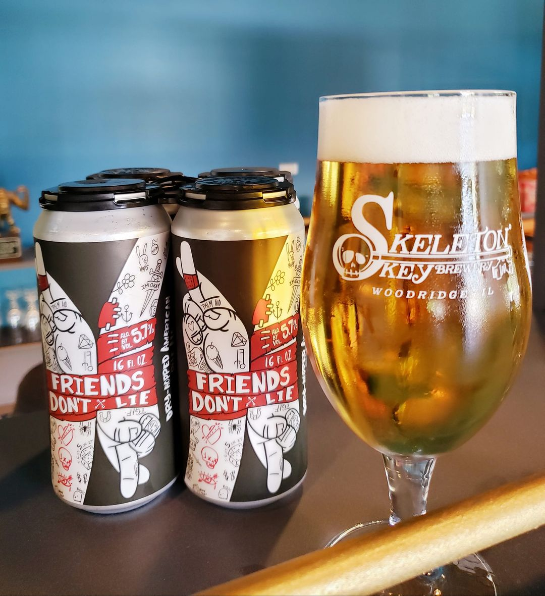 Cans and glass of Friends Dont' Lie by Skeleton Key Brewery